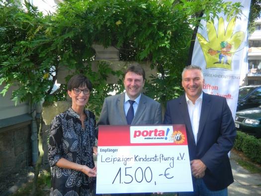 Uwe Arnold übergibt den Spendenscheck an Birgit und Alexander Malios - Leipziger Kinderstiftung
