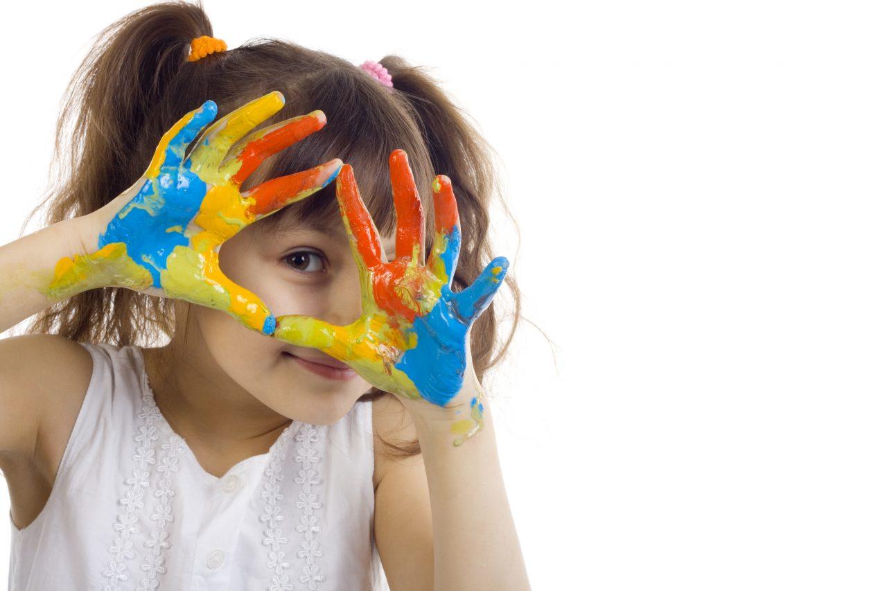kleines Mädchen schaut lächelnd durch ihre bunt angemalten Hände - Leipziger Kinderstiftung